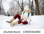 Small photo of Shot of person during falling in snowy winter park. Woman slip on the icy path, fell, injury knee and sitting in the snow. Danger of season trauma.