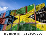 The national flag of Jamaica on a large number of metal containers for storing goods stacked in rows on top of each other. Conception of storage of goods by importers, exporters