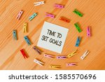 Small photo of Writing note showing Time To Set Goals. Business photo showcasing Desired Objective Wanted to accomplish in the future Colored clothespin papers empty reminder wooden floor background office.