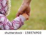 a parent holds the hand of a... | Shutterstock . vector #158576903