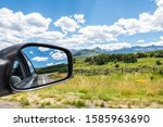 Wide angle view near Ouray, Colorado highway scenic road 550 San Juan rocky mountains range with Ridgway countryside rural fence and rear view mirror - stock photo