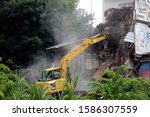 Small photo of BANDUNG, INDONESIA - DECEMBER 12, 2019: Excavator used during land execution in Tamansari. The Satpol PP forces residents to vacate his residence in a disputed land that is still in legal proceedings.
