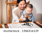 """Small photo of Asian mother is teaching baby to write Chinese with a brush. (The content of the Chinese characters on the paper is the famous """"Orchid Pavilion Preface"""" by Wang Xizhi of the Jin Dynasty)"""
