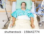 Small photo of High angle view of critical patient with endotracheal tube resting on bed in hospital