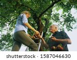 Mature Woman Handing Man An...