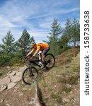 Mountain Biker Riding  A Trail...