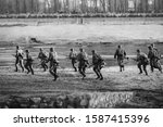 Re-enactors Dressed As German Wehrmacht Infantry Soldiers In World War II Running In Attack In Summer Day. Photo In Black And White Colors.