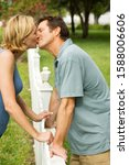 Small photo of couple kissing standing either side of fence