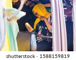 Small photo of young black African Muslim lady using mobile phone inside tricycle been in traffic