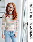 Small photo of Young woman wearing glasses and casual outfit with a good sense of humour standing laughing out loud at the camera indoors near a glass door