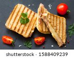 Top view photo of a club sandwich. Toasted sandwiches with salami and melted cheese on black background.