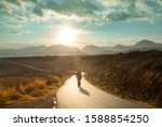 Scenic road in the mountains. Travel background. Man going on sunrise background. - stock photo