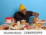 Small photo of Cheerful unshaven man points at delicious fancy cake, likes eating pastry, poses at blue background near table with freshly baked confectionery, wears stylish yellow hat, black t shirt. Sweet delicacy