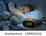Young Woman Pressing Snooze...