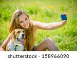 Stock photo teen girl taking photo of herself and her dog with mobile phone camera 158966090