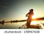 Young Man Fishing From A Boat...