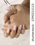 Small photo of Close up of woman with artificial fingernails washing hands