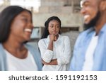 Small photo of Upset black woman watching her ex boyfriend happy in relations with new girlfriend, looking jealous on background, selective focus
