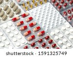 Small photo of Pills in blister packs. Blister packs full of multi-colored pills. Pharmaceutical concept. Selective focus.