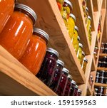 Small photo of Canned goods on wooden storage shelves in pantry