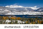 Grays and Torreys Peaks in the Colorado Rocky Mountains with Snow on Aspen Trees and Lake Dillon in the Foreground - stock photo