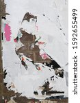 Small photo of Vertical tattered messy exposed brick wall with ripped street poster bits