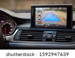 Small photo of Interior of premium car with rearview camera dynamic trajectory turning lines and parking assistant steering wheel turned right. Driver assistance parking system. Help assist options of luxury car.