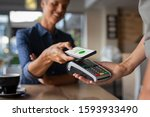 Small photo of Woman paying bill through smartphone using NFC technology in a restaurant. Satisfied customer paying through mobile phone using contactless technology. Closeup hands of mobile payment at a coffee shop