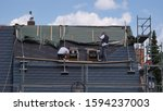 Small photo of Obercunnersdorf, Saxony / Germany - June 19, 2019: Roofers redo a slate roof in the traditional style of Upper Lusatia