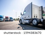 Small photo of Long haul big rig white semi truck tractor stand on truck stop parking lot across another semi trucks standing in row for truck drivers rest waiting for the continuation of the cargo delivery route