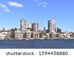 Small photo of Town houses and apartment buildings on the shore of Sydney harbour from a boat in late afternoon sun