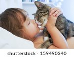 Stock photo child is kissing a cat 159490340