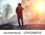 A Man Is Wearing A Cowboy Hat...