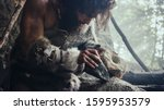 Small photo of Primeval Caveman Wearing Animal Skin Hits Rock with Sharp Stone and Makes Primitive Tool for Hunting Animal Prey. Neanderthal Using Hand axe to Create first Wheel.