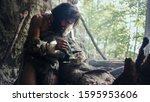 Small photo of Primeval Caveman Wearing Animal Skin Hits Rock with Sharp Stone and Makes First Primitive Tool for Hunting Animal Prey or to Handle Hides. Neanderthal Using Handax. Dawn of Human Civilization