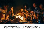 Neanderthal or Homo Sapiens Family Cooking Animal Meat over Bonfire and then Eating it. Tribe of Prehistoric Hunter-Gatherers Wearing Animal Skins Eating in a Dark Scary Cave at Night