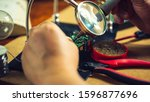 Small photo of Hands of man holding solder iron soldering the pin on electronics circuit board, DIY hobbies and electrician workshop concept.