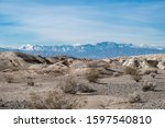 USA, Nevada, Clark County, Tule Springs Fossil Beds National Monument: White gypsum hills with Mt. Charleston in the distance.