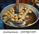 Small photo of Top view fried pock balls on heat pot at night market in Thailand. Delicious street pock ball at night market.