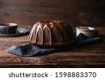 Small photo of Delicious dessert, dark chocolate bundt cake topped with ganache glaze on rustic wooden background