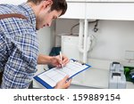 handsome young plumber writing... | Shutterstock . vector #159889154
