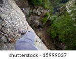 A foot on a ledge of a very high rock face - stock photo