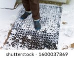 Small photo of A man wearing goloshes and wool socks standing on the doormat covered with snow