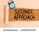 Small photo of Writing note showing Systematic Approach. Business photo showcasing A process used to determine the viability of a project Alarm clock and torn cardboard on a wooden classic table backdrop.