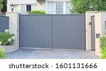 Small photo of Automatic swing open front security gate across a driveway