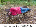 Man Sleeping On A Bench In A...