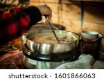 Small photo of Side view close up of homemade healthy soup in big metallic pot. Hand is stirring the meal with scoop while it is boiling. Blurred kitchen and dishes in the background.