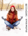 young woman in a lotus position on the snow - stock photo