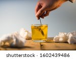 Small photo of A hand stirring orange effervescent medicine with a spoon. Surrounded by some tissue papers. Good Health Concept. Cold season. Selective Focus