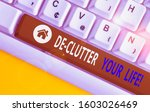 Small photo of Writing note showing De Clutter Your Life. Business photo showcasing remove unnecessary items from untidy or overcrowded places White pc keyboard with note paper above the white background.